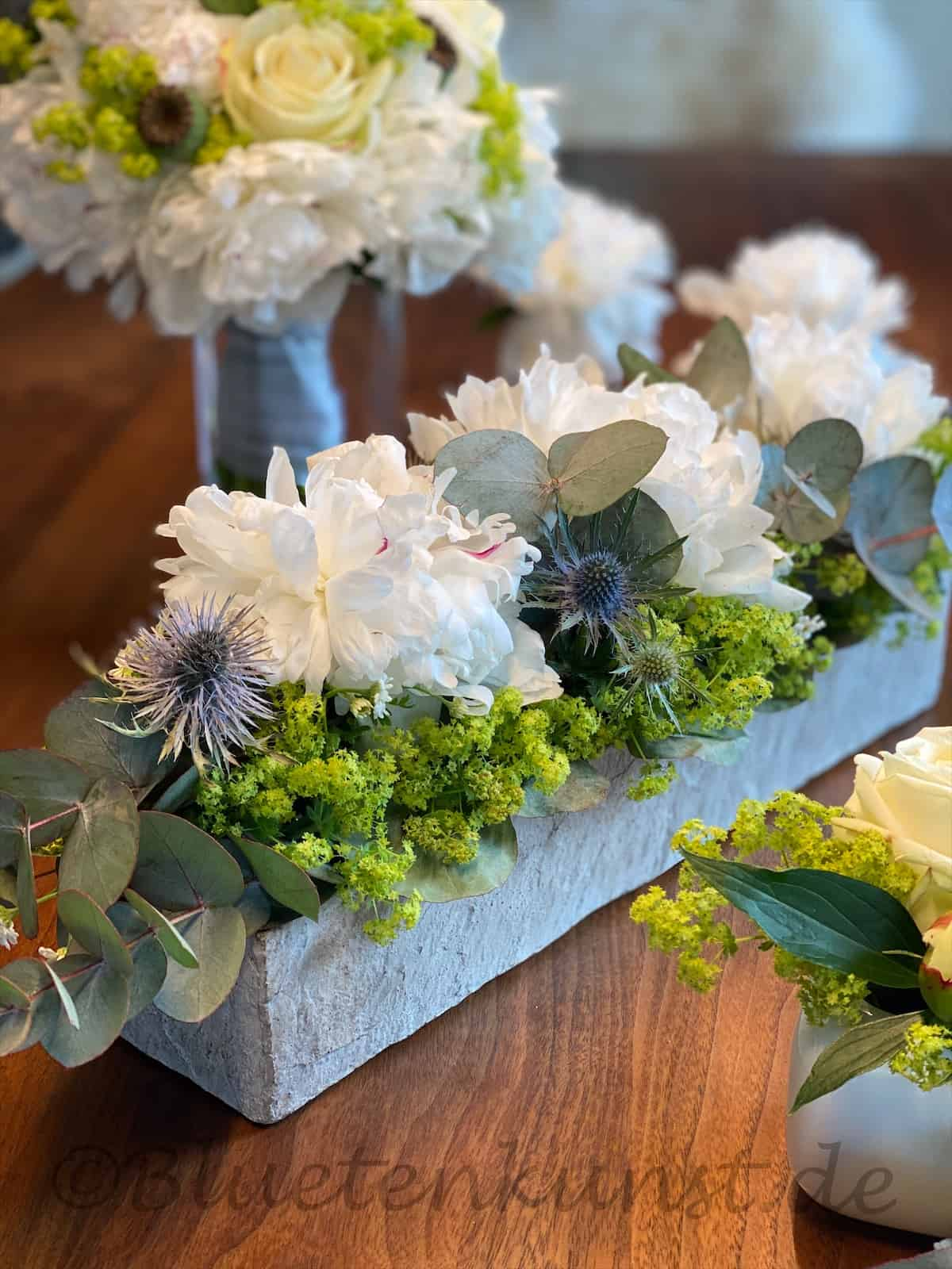 Edle weiße Tischdekoration für Hochzeit edle Pfingstrose in weiß mit Eucalypthus und Frauenmantel, Distel Mannstreu blau