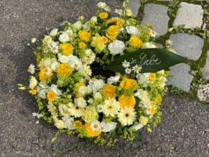 moderne trauerfloristik urne kranz aus Pfaffenhofen mit gelben Rosen und Gerbera von Gerti Haslauer