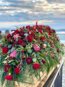 Sargbukett modern mit roten Rosen, Gerbera, Protea, Zuckerbusch, Skimmie, Ilex, Eukalyptus, Seidenkiefer auf einem Holzsarg - von Fotograf: Nicole Kemeder https://www.nickisbluetenzauber.com/