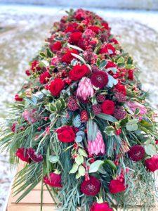 stilvolle und moderne Trauerfloristik Sargschmuck Blumenbukett für Beerdigung mit roten Rosen, Gerbera, Protea, Zuckerbusch, Skimmie, Ilex, Eukalyptus, Seidenkiefer auf einem Holzsarg - Fotograf: Nicole Kemeder https://www.nickisbluetenzauber.com/