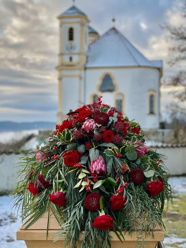 Trauerfloristik Sargblumenschmuck modern mit roten Rosen, Gerbera, Protea, Zuckerbusch, Skimmie, Ilex, Eukalyptus, Seidenkiefer auf einem Holzsarg im Hintergrund ist eine bayrische Friedhofskapelle zu sehen - Fotograf: Nicole Kemeder https://www.nickisbluetenzauber.com/
