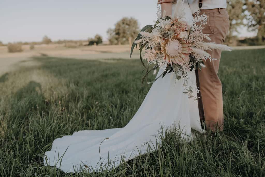 Boho Style Hochzeitsfotoshooting auf Wiese in den Paarauen bei Hohenwart mit Brautpaar Daniela und Tom - Daniela hält einen Hammer Brautstrauß mit Kings Protea , Trockenblumen , Olive