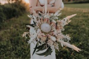 gigantischer Hochzeits blumenstrauss im vintage boho style mit königs protea , pampasgras und trockenblumen