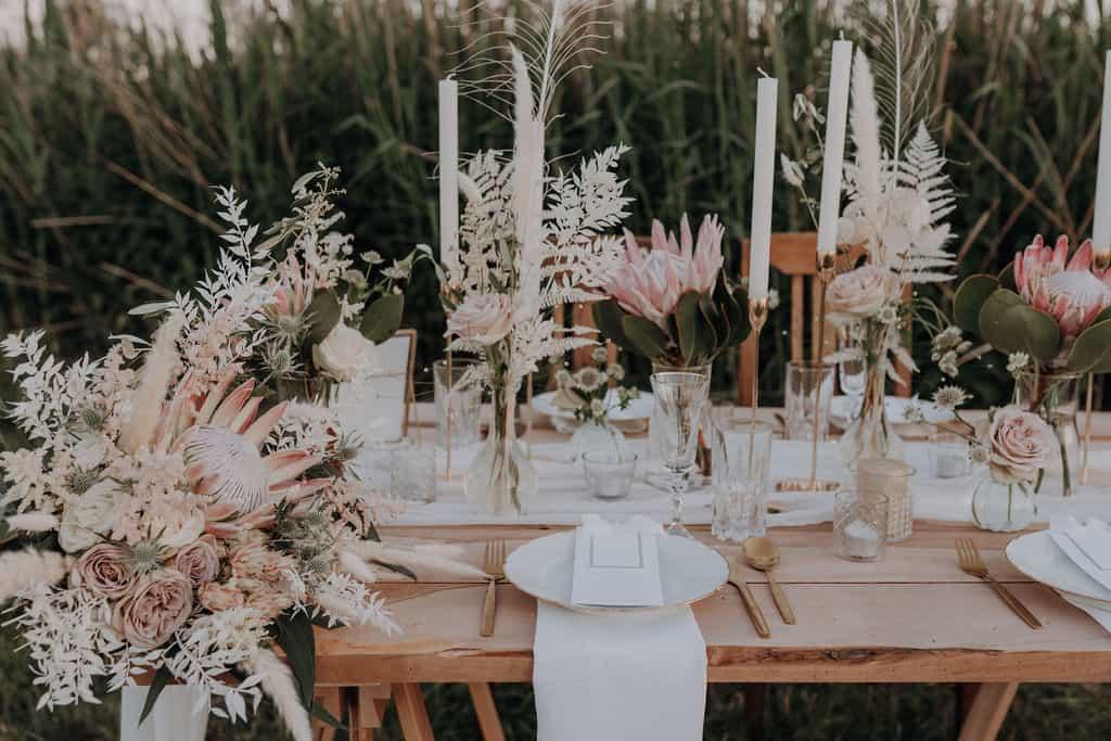 Boho und vintage traum hochzeitsdekoration Ingolstadtmit Protea vom florist für freie zeromonie mit goldbesteck , weißen kerzen und goldständer , Trockenblumen , tischplatte aus nußbaum holz auf finnvard
