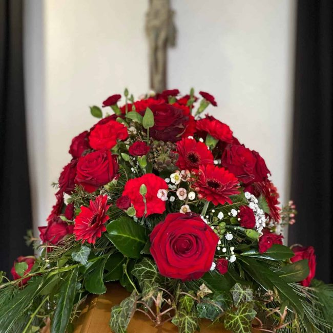 Sargbouquet klassisch mit roten Rosen, Gerbera für christliche Trauerfeier in Baar-Ebenhausen