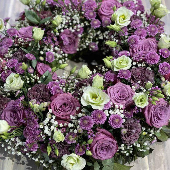 Moderne Trauerfloristik - stilvoller Kranzin violett - lila mit Rosen, Lisianthus, Schleierkraut, Nelken, Chrysamtheme