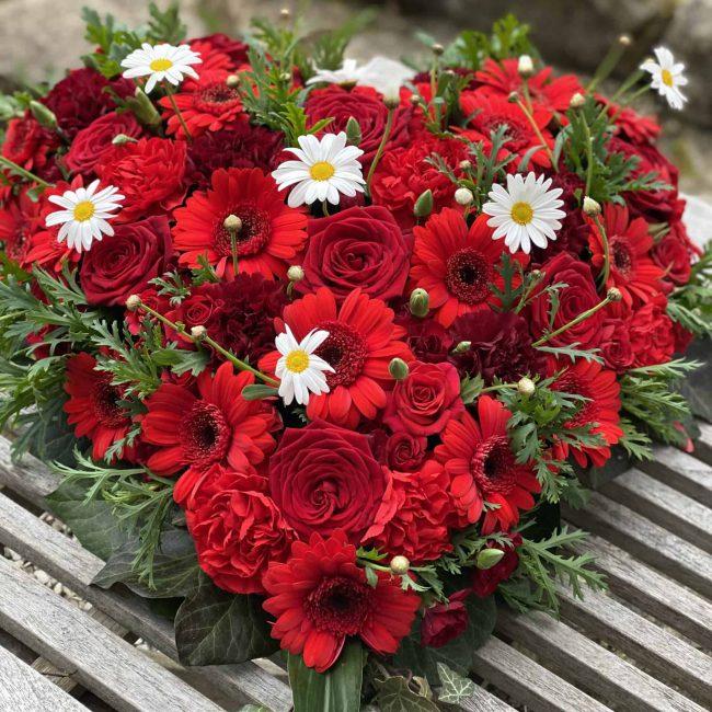 Trauergesteck Herz in rot mit Rosen und gebera und weißer kamile