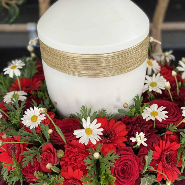 Urnenkranz in rot mit rosen, gerbera und weißer kamile - weiße urne für christliche beerdigung in paffenhofen ilm