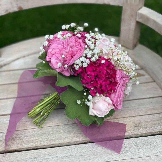 zeigt pink Brautstrauss mit Rosen