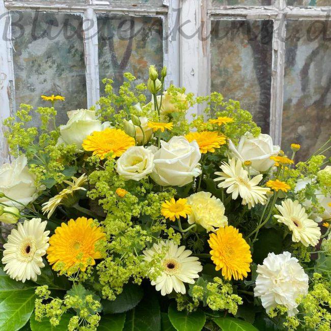 moderne Trauergestecke mit gelben Blumen Rosen, Gerbera im Hintergrund ein vintage Fenster für Beerdigung in Schrobenhausen moderne Trauerfloristk